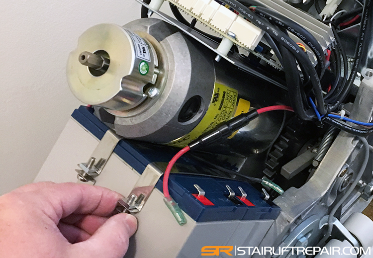 Service tech replacing stairlift batteries